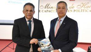 El ministro de Hacienda, Donald Guerrero Ortiz, entrega un ejemplar de la Carta Compromiso al Ciudadano al ministro de Administración Pública, Ramón Ventura Camejo.
